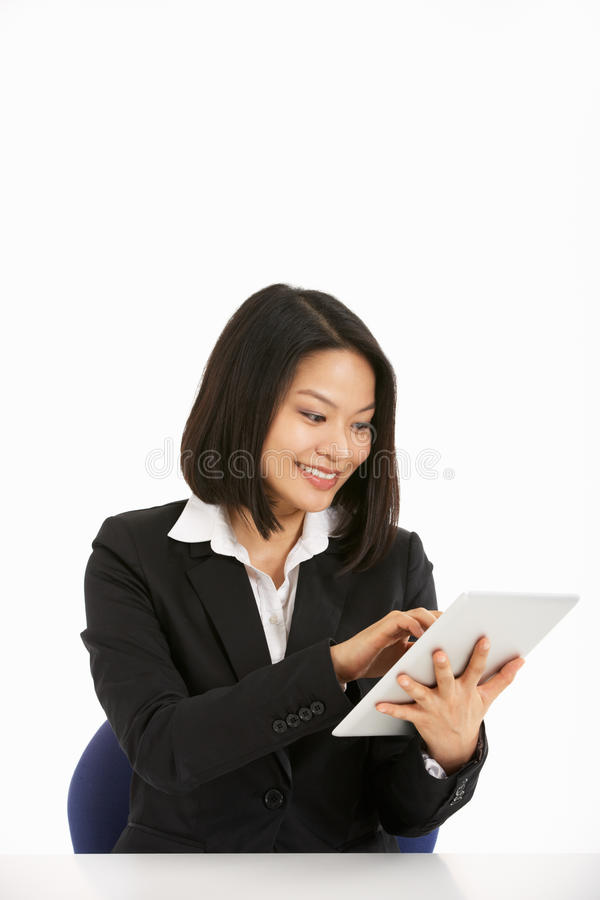 Mulher de negócios chinesa que trabalha no computador da tabuleta fotos de stock