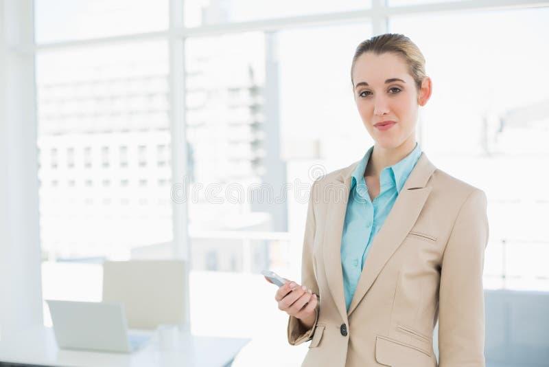Mulher de negócios chique bonita que guarda seu smartphone que sorri na câmera fotos de stock royalty free