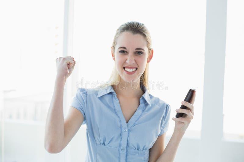 Mulher de negócios chique Cheering que guarda seu smartphone fotografia de stock