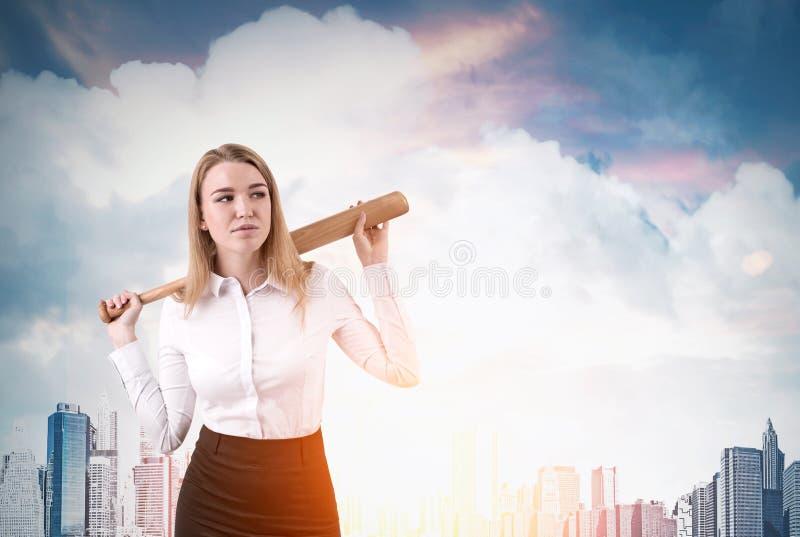A mulher de negócios com bastão de beisebol está estando na cidade foto de stock