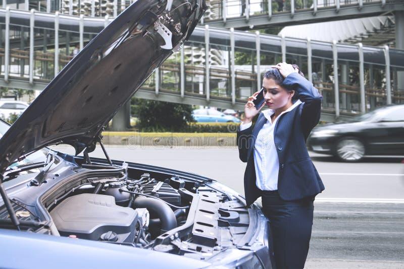 Mulher de negócios com carro quebrado que chama uma ajuda fotos de stock royalty free