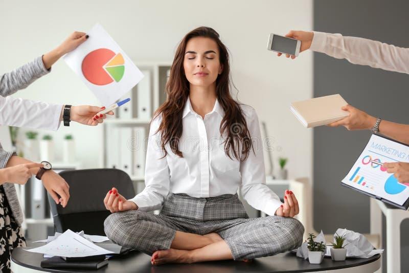 Mulher de negócios com muito trabalho para fazer meditar no escritório fotos de stock royalty free