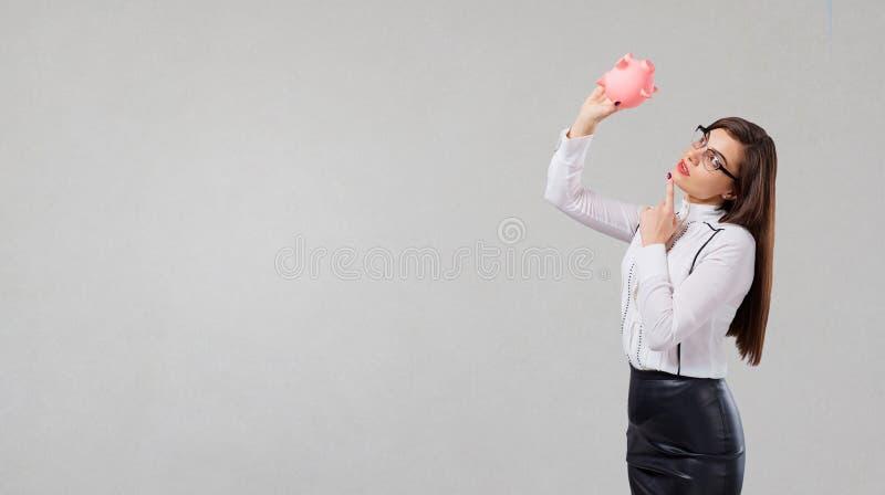 Mulher de negócios com o mealheiro nas mãos em um fundo cinzento imagem de stock