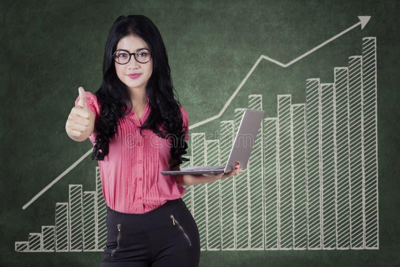 Mulher de negócios com o polegar ascendente e um gráfico de lucro fotos de stock royalty free