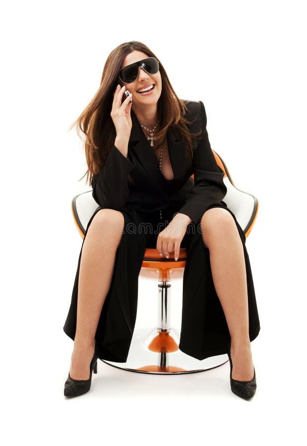 Mulher de negócios com o telefone na cadeira alaranjada fotografia de stock