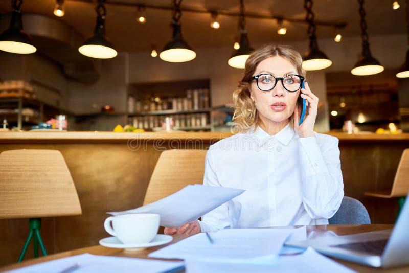 Mulher de negócios com os papéis que falam no telefone fotos de stock royalty free