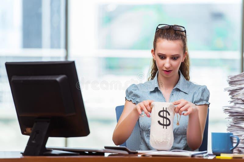 A mulher de negócios com os sacos do dinheiro no escritório imagens de stock royalty free