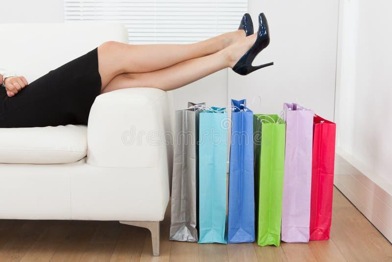 Mulher de negócios com pés sobre multi sacos de compras coloridos imagens de stock royalty free