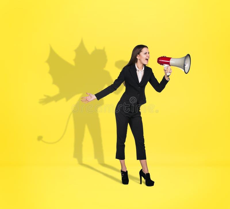 Mulher de negócios com sombra do diabo atrás da parte traseira fotografia de stock royalty free