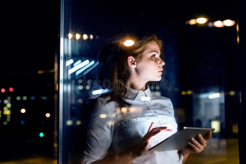 Mulher de negócios com a tabuleta que trabalha tarde na noite fotografia de stock royalty free