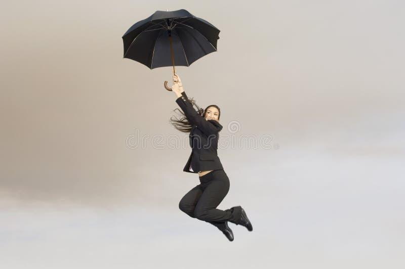 Mulher de negócios com um guarda-chuva no meio do ar imagem de stock