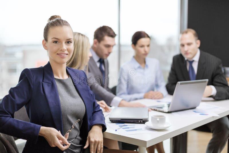Mulher de negócios com vidros com a equipe na parte traseira imagem de stock royalty free