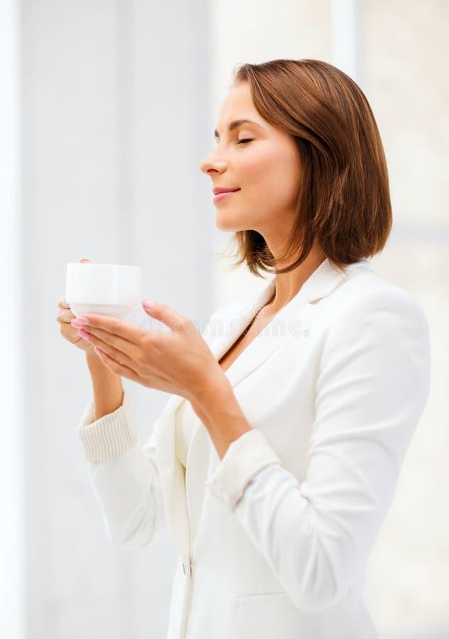 Mulher de negócios com a xícara de café no escritório fotografia de stock