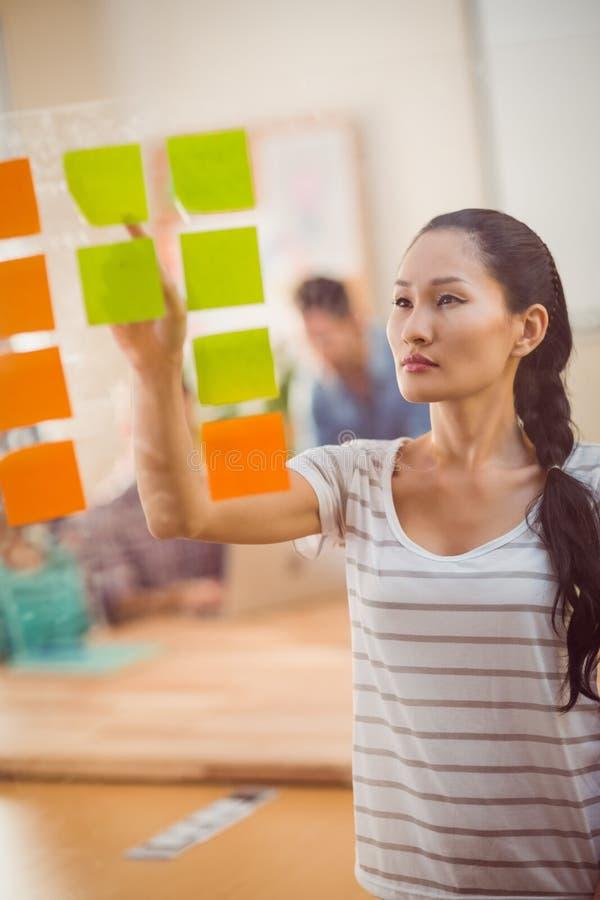 Mulher de negócios concentrada que aponta post-it na parede fotografia de stock