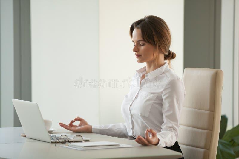Mulher de negócios consciente calma que medita na mesa de escritório com olhos c fotos de stock