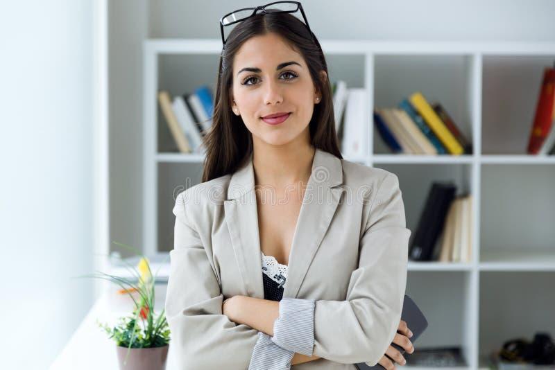 Mulher de negócios consideravelmente nova que olha a câmera no escritório imagens de stock