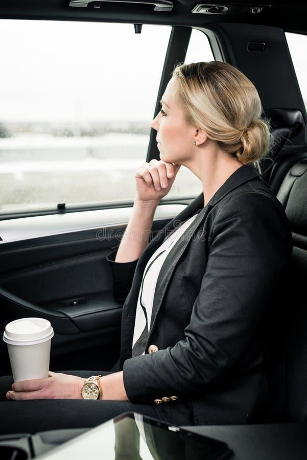 Mulher de negócios contemplada que guarda o copo de café que senta-se no carro imagem de stock royalty free