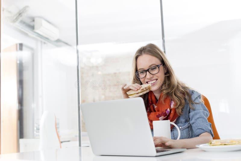 Mulher de negócios criativa que come o café da manhã ao trabalhar no portátil no escritório fotos de stock royalty free