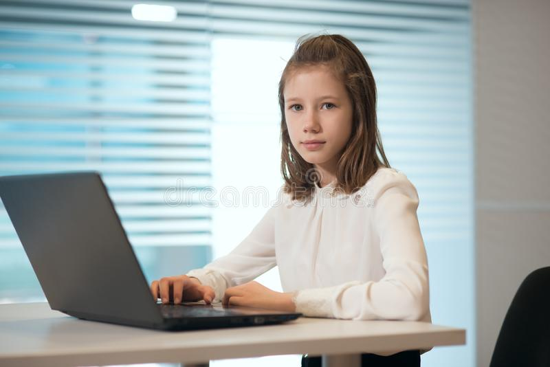 Mulher de negócios da moça na roupa ocasional, sentando-se em um olhar da tabela proximamente nos originais, trabalhando no compu foto de stock