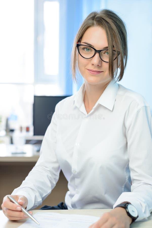 Mulher de negócios de sorriso atrativa nova no branco que assina o original no escritório moderno brilhante fotografia de stock royalty free