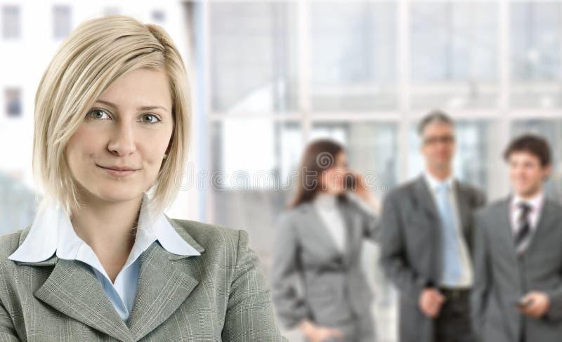 Mulher de negócios de sorriso com colegas de trabalho fotografia de stock royalty free
