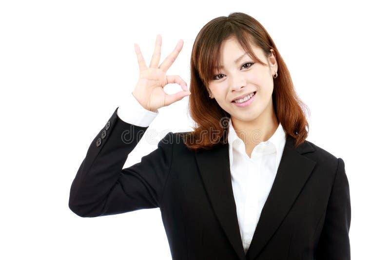 Mulher de negócios de sorriso com gesto aprovado fotografia de stock royalty free