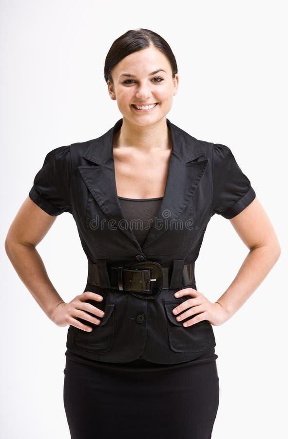 Mulher de negócios de sorriso com mãos nos quadris fotografia de stock royalty free