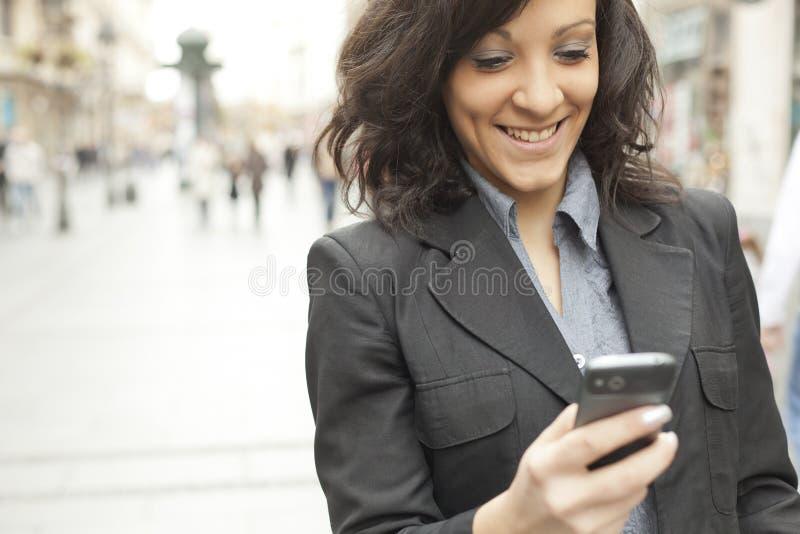 Mulher de negócios de sorriso com o smartphone na rua imagem de stock