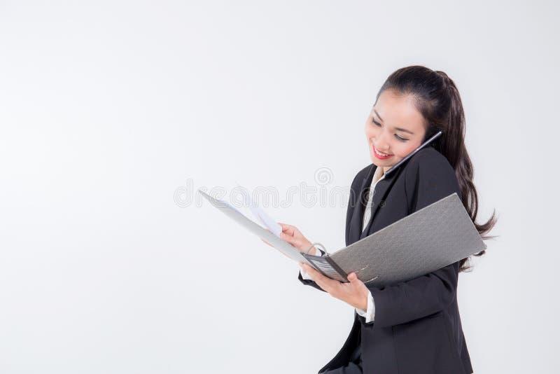 a mulher de negócios de sorriso está falando pelo smartphone e pelo arquivo de terra arrendada imagens de stock