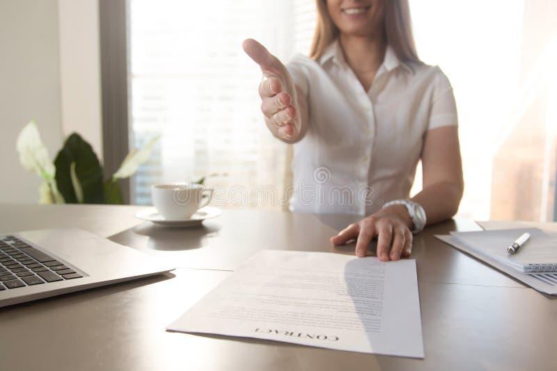 Mulher de negócios de sorriso que dá a mão para o aperto de mão, oferecendo contra fotografia de stock royalty free