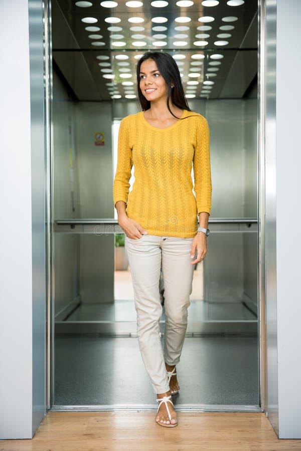 Mulher de negócios de sorriso que está no elevador foto de stock