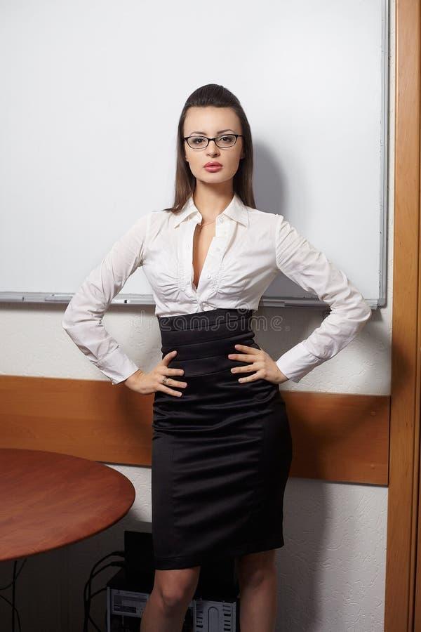 Mulher de negócios de sorriso que está a placa próxima foto de stock