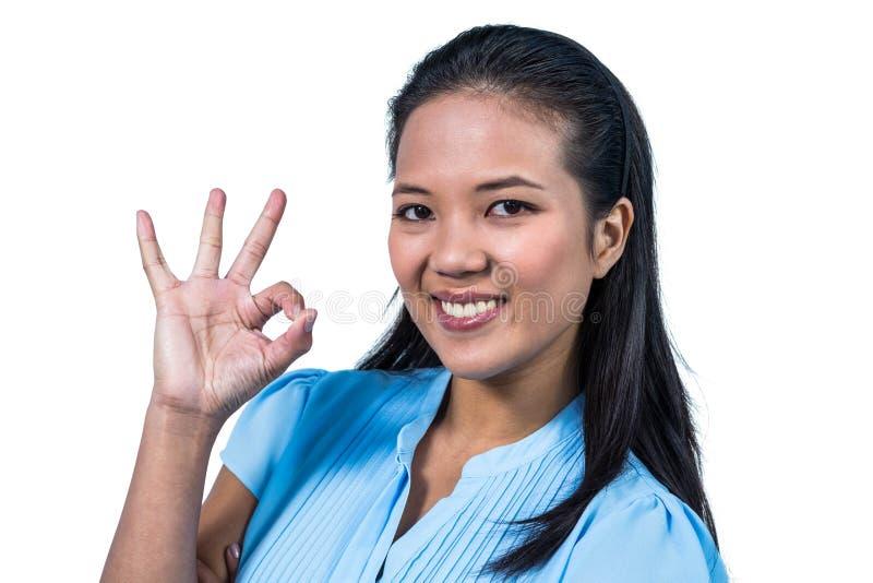 Mulher de negócios de sorriso que faz o sinal aprovado fotos de stock