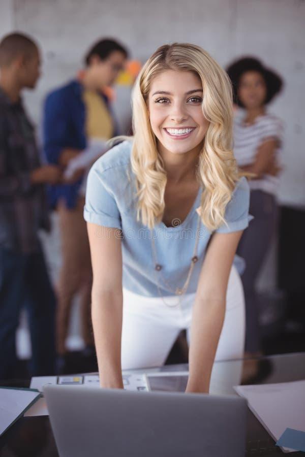 Mulher de negócios de sorriso que inclina-se na tabela no escritório fotos de stock royalty free