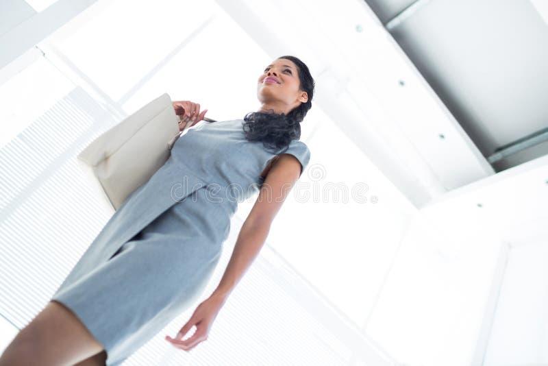 Mulher de negócios de sorriso que sae do escritório foto de stock royalty free