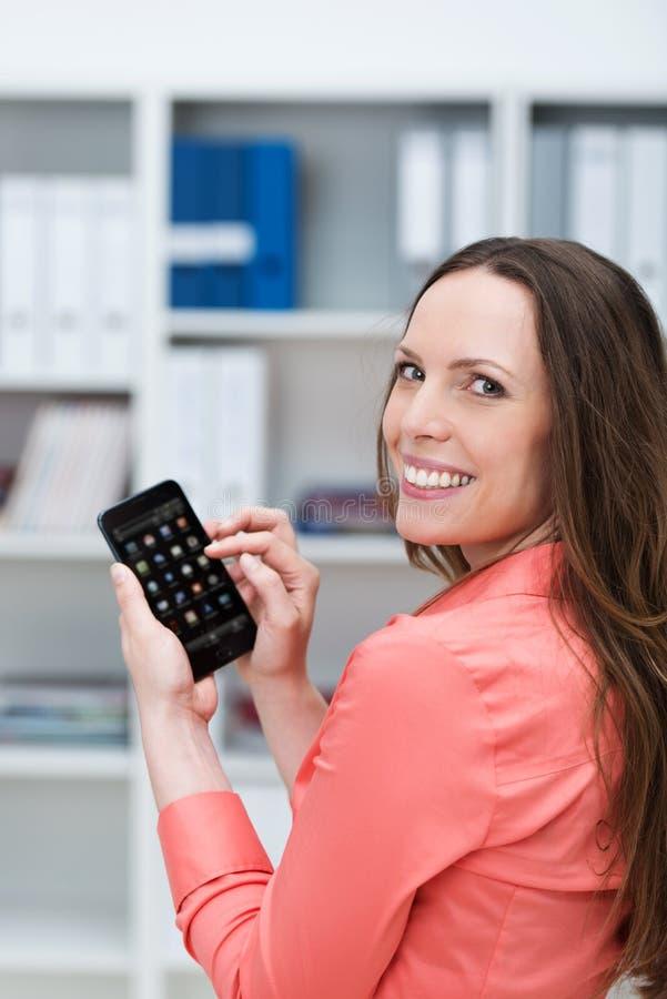 Mulher de negócios de sorriso que texting em seu smartphone imagem de stock royalty free