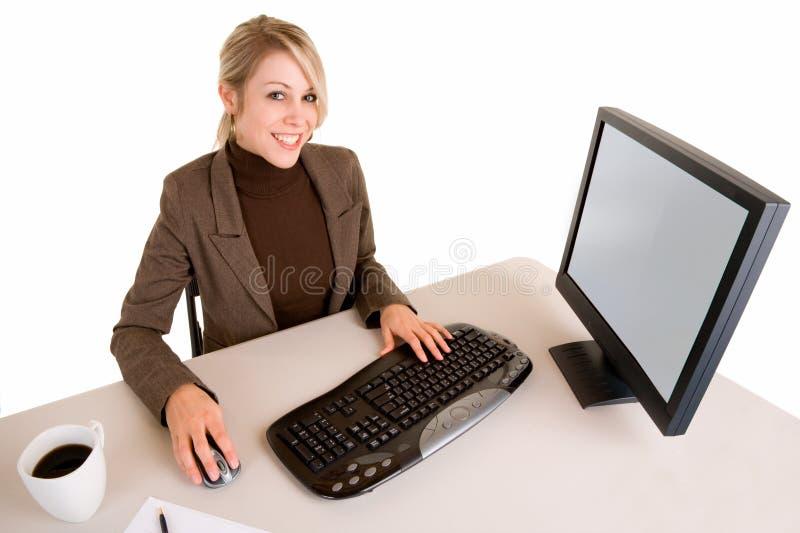 Mulher de negócios de sorriso que trabalha em seu computador fotografia de stock