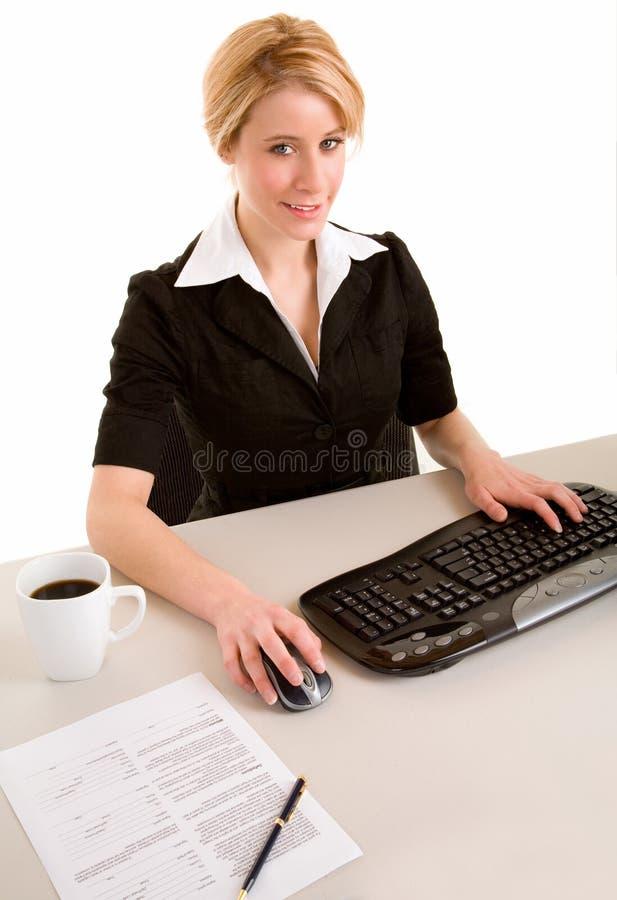 Mulher de negócios de sorriso que trabalha em seu computador imagens de stock