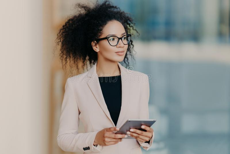 A mulher de negócios descascada escura elegante atrativa usa a tabuleta digital, vestida no vestuário formal, suportes no escritó imagens de stock royalty free