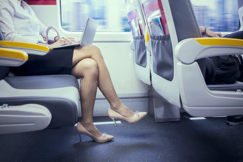 Mulher de negócios desconhecida com o portátil no trem imagem de stock royalty free