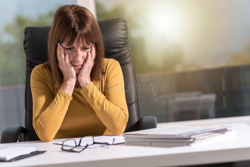Mulher de negócios desesperada com cabeça nas mãos, efeito da luz imagem de stock