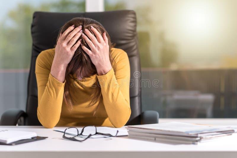 Mulher de negócios desesperada com cabeça nas mãos, efeito da luz fotografia de stock royalty free