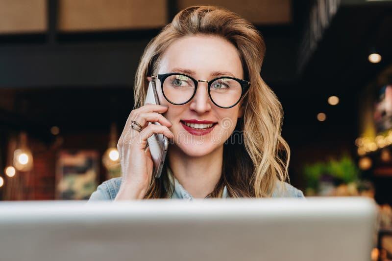 Mulher de negócios do retrato nos vidros que sentam-se no café na frente do portátil, falando no telefone O blogger da menina com fotos de stock