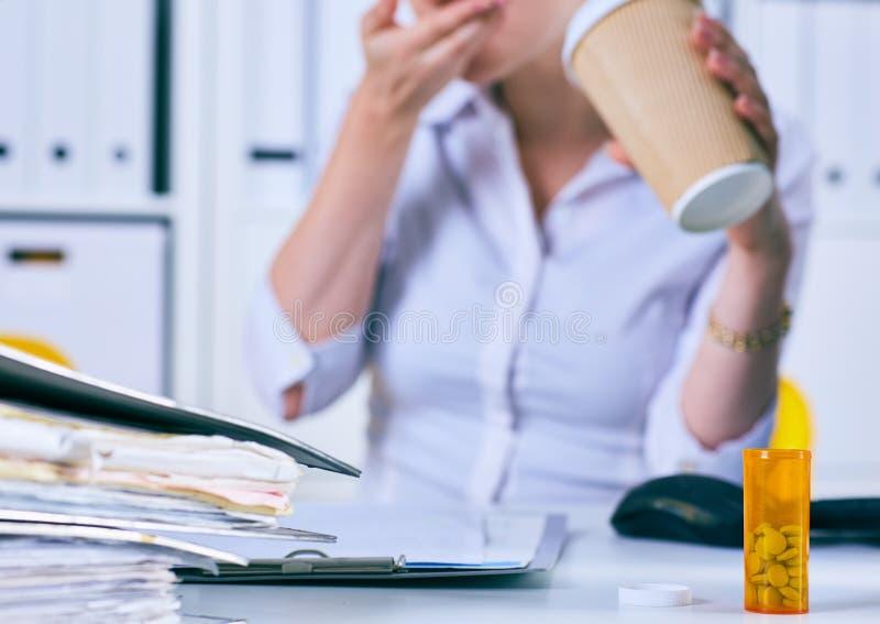 Mulher de negócios doente que guarda a xícara de café e o comprimido médico no local de trabalho Apenas cede a tabela foto de stock