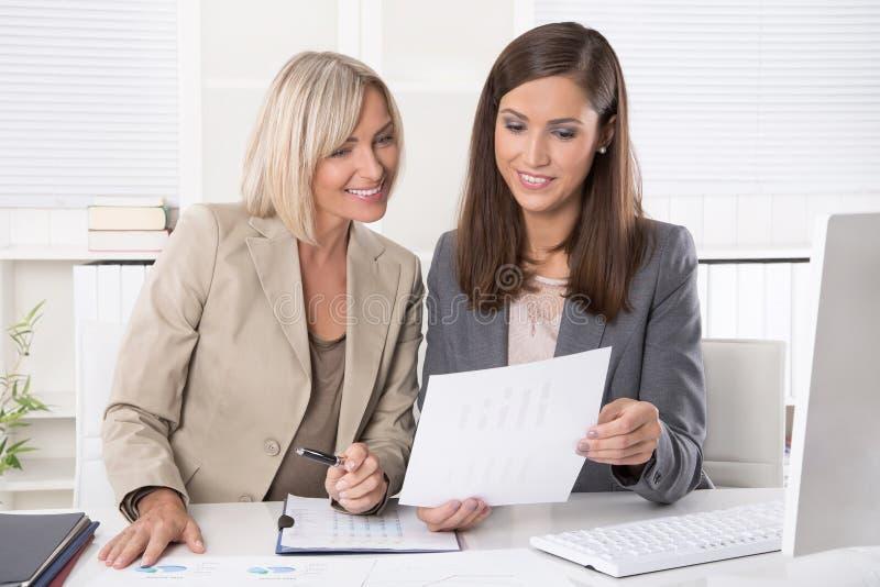 Mulher de negócios dois atrativa que senta-se em um funcionamento do escritório imagem de stock