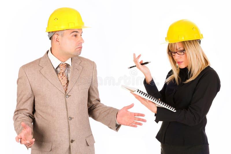 Mulher de negócios e arquiteto irritados fotografia de stock