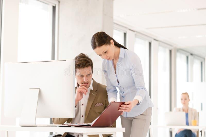 Mulher de negócios e homem de negócios que reveem o arquivo na mesa do computador no escritório fotografia de stock