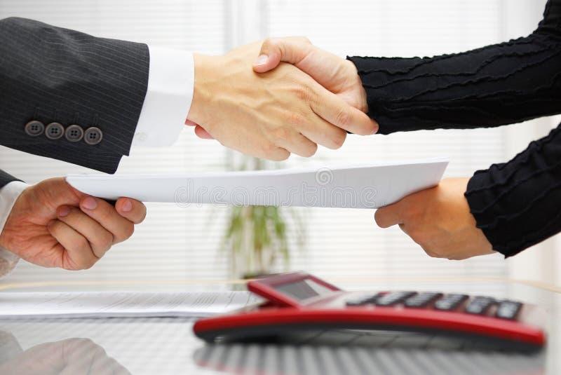 A mulher de negócios e o homem de negócios são aperto de mão e engodo da troca fotografia de stock