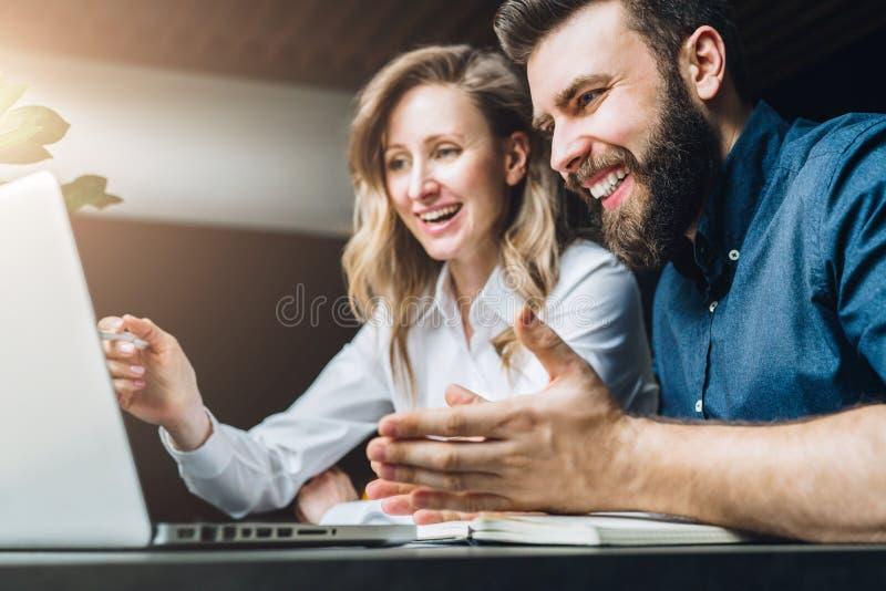 A mulher de negócios e o homem de negócios estão sentando-se na mesa contra o portátil e estão discutindo-se o projeto do negócio imagens de stock royalty free