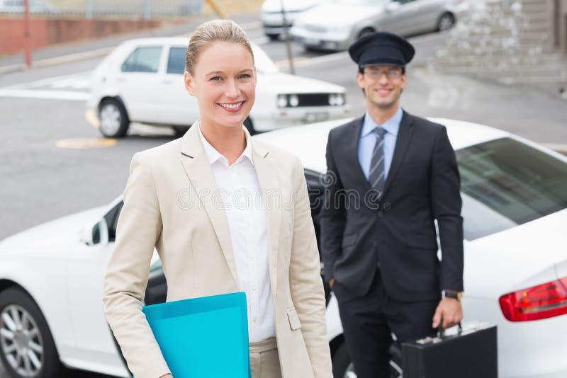 Mulher de negócios e seu motorista que sorriem na câmera imagens de stock royalty free